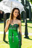 Girl in green dress walking park with white umbrella. Stock Image