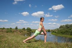 Girl in green exercising against the sky Royalty Free Stock Photo