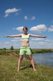Girl in green exercising on meadow Stock Image