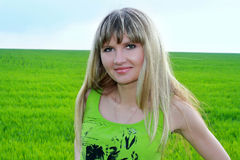 Girl and green field Royalty Free Stock Image