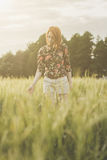 Girl and green field in the evening Stock Photos
