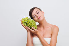 Girl with green grapes. Royalty Free Stock Images