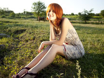 Girl at green grass field at sunset. Royalty Free Stock Photos