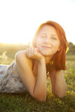 Girl at green grass field at sunset. Stock Photos