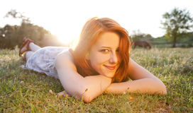 Girl at green grass field at sunset. Royalty Free Stock Images