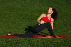 Girl on green grass. morning exercise. Woman practices yoga in nature Royalty Free Stock Image