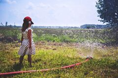 Girl on Green Grass Near Red Hose While Pumping Water during Daytime Royalty Free Stock Photo