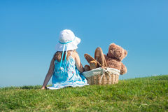 Girl on green grass with teddy bear in basket Royalty Free Stock Photo