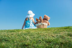 Girl on green grass with teddy bear in basket Stock Images