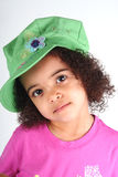 Girl in Green Hat. Close up of a young toddle girls brown eyes Stock Photo