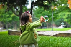 Girl in Green Hoodie Holding Bubbles during Daytime Royalty Free Stock Images