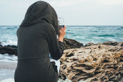 Girl in the green hoodie sitting on the beach photographing the sea Royalty Free Stock Image
