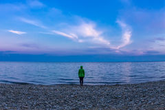 The girl in the green jacket is an authentic one in the blue sea. At sunset Stock Photos