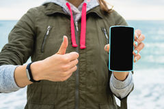 Girl in the green jacket on the beach showing the mobile phone s Royalty Free Stock Photography