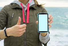 Girl in the green jacket on the beach showing the mobile phone screen Stock Photo