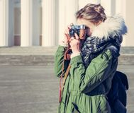The girl in the green jacket photographs vintage camera outdoors on a sunny spring day. Close up Stock Photo