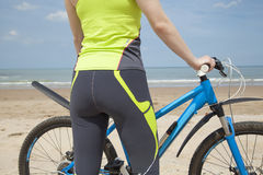 Girl in a green jumpsuit with a blue bicycle on the beach Royalty Free Stock Image