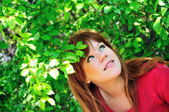 Girl in green leaves Stock Image