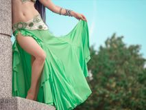 Girl in a green, lime dress for belly dancing poses at a marble pillar stock photo