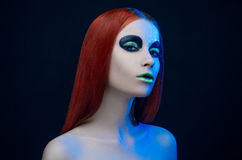 Girl green makeup red hair blue background Stock Images