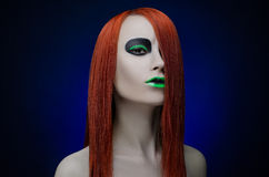 Girl green makeup red hair blue background Stock Photography