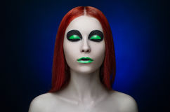 Girl green makeup red hair blue background Stock Photo