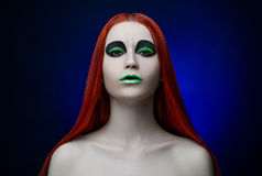 Girl green makeup red hair blue background Royalty Free Stock Photography
