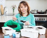Girl in green making soil for seedlings Stock Photos