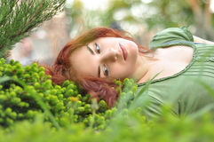 Girl on a green meadow. Red-haired woman lying in grass Stock Photo