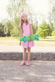Girl with green penny skateboard Royalty Free Stock Photo
