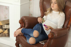 Girl with green and pink fidget spinners in hands, indoors, wearing white shirt and jeans stock images