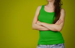 A girl in a green plain t-shirt. Empty tank top. Closeup. Isolat Stock Photos