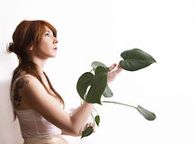 Girl with green plant on white background Stock Photo