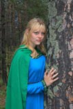 The girl in the green raincoat, nestled on a pine Royalty Free Stock Photography