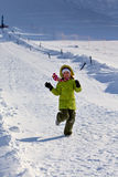 Girl in green running in the snow Royalty Free Stock Images