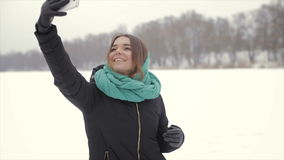 The girl in the green scarf and a black jacket makes selfie stock video footage