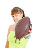 Girl in green shirt shows brown rugby ball towards camera Stock Image