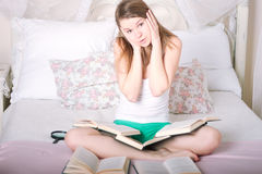 Girl on the bed reading a book Stock Image