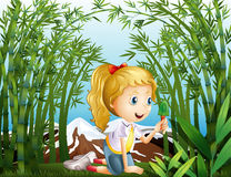A girl with a green shovel kneeling in the rainforest Stock Image