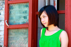 Girl in a green skirt. Girl stands in front of a red window Stock Image
