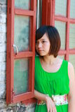 Girl in a green skirt. Girl stands in front of a red window Royalty Free Stock Images