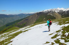 Girl on the green slope with snow in spring Pyrenees Royalty Free Stock Image