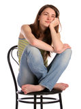 Girl in green stripy top sit on stool dreaming. Stock Image
