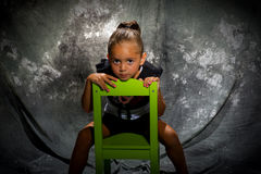 Girl in green studio chair Stock Images