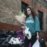 The girl in green sweater bought a flower at Columbia road flower market. LONDON, ENGLAND - JULY 12, 2016 The girl in green sweater bought a flower at Columbia Royalty Free Stock Images