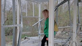 A girl in a green sweater wanders through the ruined abandoned building and looks around. From the building there was only one frame stock video