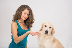 Young woman gives a piece of meat to her dog stock photo