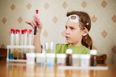 Girl looks anxiously at test tube. Girl in green t-shirt looks anxiously at test tube with specimen in her hand Royalty Free Stock Images