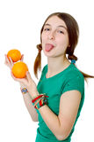 Girl in green t-shirt shows tongue holds orange Royalty Free Stock Images