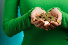 Girl in green turtleneck holding gold coins in hands. Isolated on green grunge background Stock Image